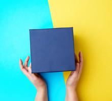 Two Female Hands Hold A Closed Dark Blue Paper Cardboard Box
