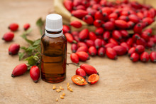 Rose-hips And Rose Hip Seed Oil On The Wooden Table. Rose Hip  Commonly Known As Rose Hip (Rosa Canina).