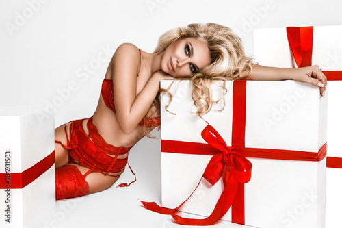Beautiful young blonde woman in sexy red lingerie standing next to white christmas presents. Christmas glamour photo. A lot of gifts. - Image