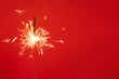 Leinwanddruck Bild - Close up of Brightly burning sparkler on a red background with lots of sparks.