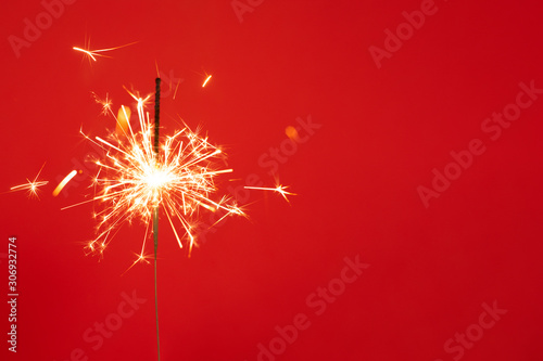 Fototapeta Close up of Brightly burning sparkler on a red background with lots of sparks. obraz