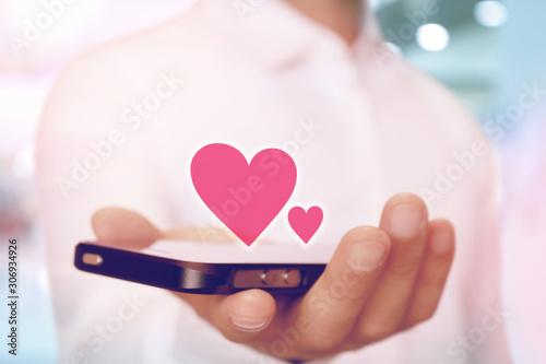 スマートフォンでハートの通知マーク SNS heart on smartphone SNS app Fotobehang