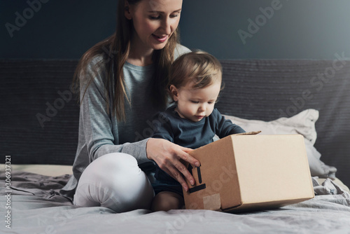 Photo Mother and child sitting on bed and unwrapping package