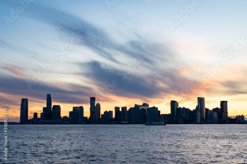 Jersey City Skyline along the Hudson River during a Sunset with a Ferry Boat Fototapet