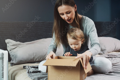 Woman and baby unpacking cardboard box with surprise Canvas Print