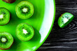 canvas print picture - exotic fruit design with sliced kiwi on green plate dark table background top view