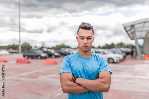 Fototapeta male athlete, resting after workout, looking confidently, strong and willed look, workout summer in the city. Fitness motivation youth lifestyle. Free space for copy text. obraz na płótnie