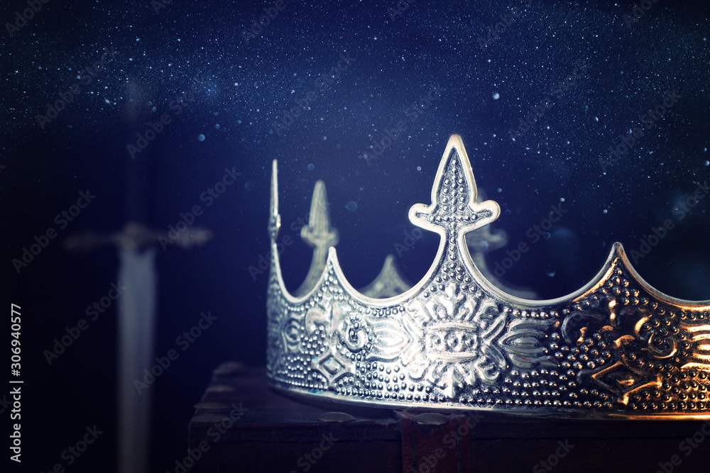 Fototapeta low key image of beautiful queen/king crown over antique box next to sword. fantasy medieval period. Selective focus