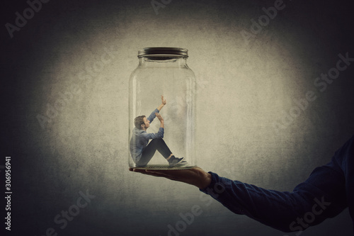 Fotografia Business concept with a scared tiny man trapped inside a glass jar held by his gigantic boss hand