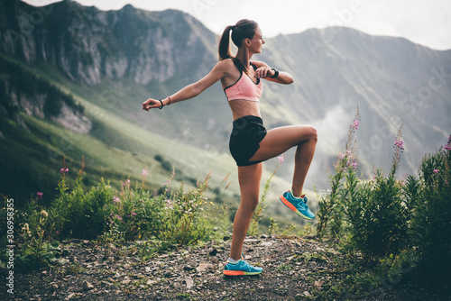 Girl runner warm up outdoor. Young female runner stretching arms before running at the mountain. Athlete at the top of the mountain.