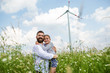 canvas print picture - Mature father with small daughter standing on field on wind farm.