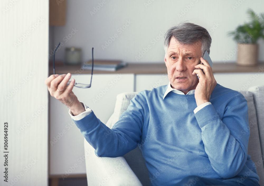 Fototapeta Senior Man Having Unpleasant Phone Conversation Sitting On Couch Indoor