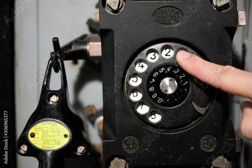 Photo Finger wählt eine Zahl auf der Wählscheibe eines alten schwarzen Telefons in ein