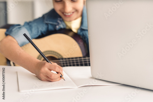 Fotografía  Kid making notes during online music lesson
