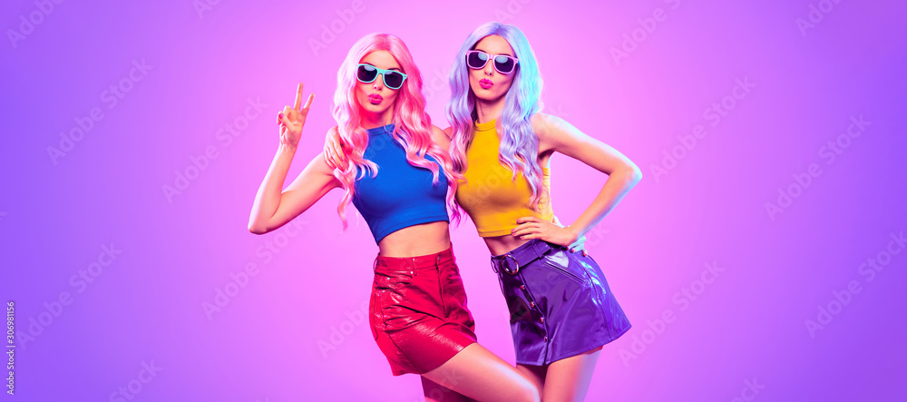 Fototapeta Gorgeous Disco Party girl with Having Fun, neon style. Pink Purple hairstyle. High Fashion. Two young beautiful model woman friends Dance, colorful neon Light. Night Clubbing.Pop Art fashionable Style