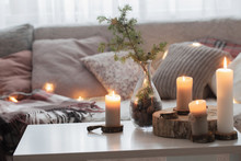 Composition Of Candles On  White Table Against The Background Of