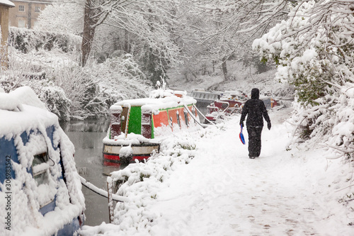 Fotomural Woman walking in heavy snow on the Kennet and Avon towpath in Bath, England, UJK