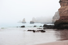 Rocks On The Shore Of Atlantic Ocean In Misty Morning In Algarve, Portugal. Beautiful Summer Landscape