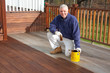 canvas print picture - painter staining a deck in the spring