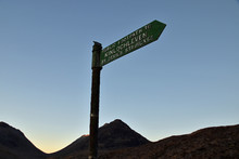 Signpost For Public Footpath To Kinlochleven Via The Devil's Staircase. This Is Part Of The Famous West Highland Way Long Distance Walking Route. Taken At Sunrise With Mountain Backdrop.