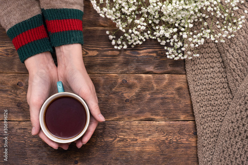 Recess Fitting Tea Female hands in sweater with a cup of hot tea above wooden table background.