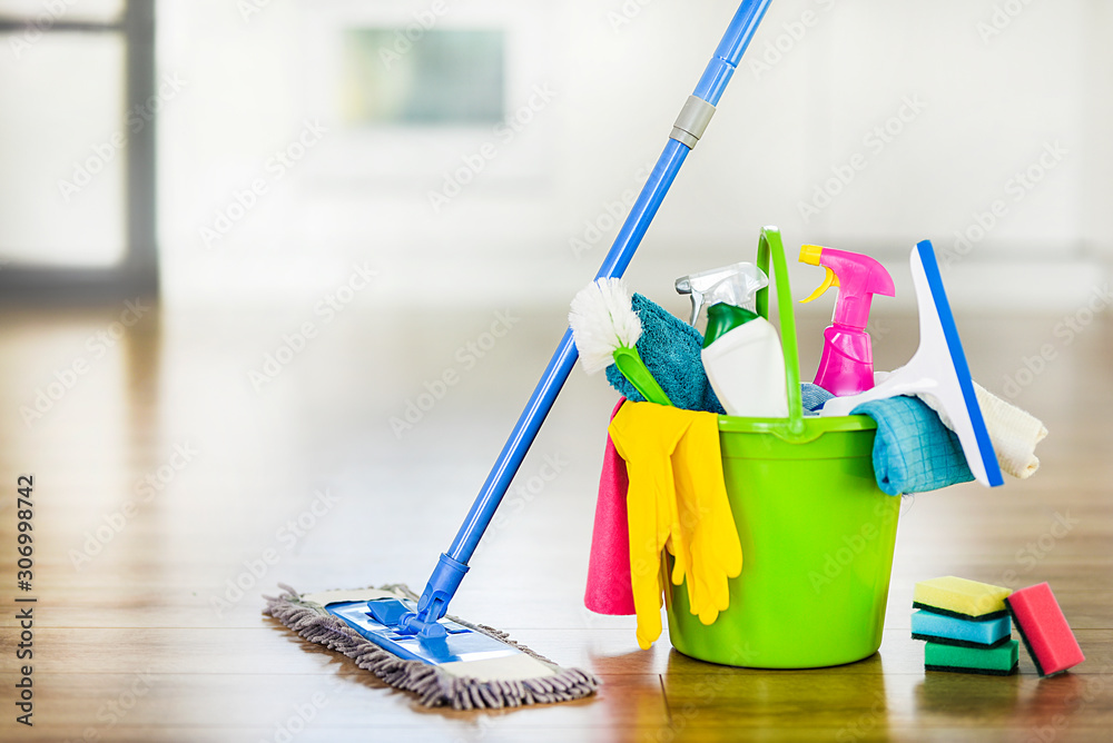 Fototapeta Bucket with cleaning items on blurry modern kitchen background. Washing brush and spray set with copy space.
