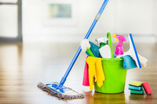 Bucket With Cleaning Items On Blurry Modern Kitchen Background. Washing Brush And Spray Set With Copy Space.