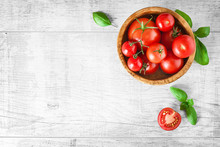Fresh Tomatoes And Basil In Olive Bowl On White Table, Top View. Beautiful Red Tomato Vegetables Concept With Copy Space.
