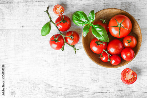 Fototapeta Fresh red variety tomatoes with basil on white rustic table. Tomato vegetable concept space for text or banner top view. obraz