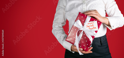 Cadres-photo bureau Pays d Asie Secret Santa concept - female in office clothes holding wrapped present red background, copy space