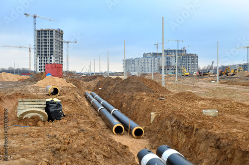 Laying underground storm sewers at a construction site. Groundwater system for new residential buildings in the city. Installation of water main, sanitary sewer, storm drain systems in city.