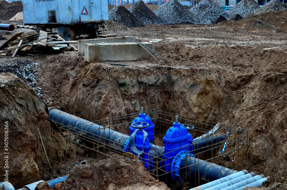 Fototapeta Laying underground storm sewers at a construction site. Groundwater system for new residential buildings in the city. Installation of water main, sanitary sewer, storm drain systems.