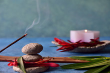 Relaxation And Spa Concept. Water Style Background, Stacked Stones In Equilibrium, Incense And Lit Candle, Leaves And Petals In Stone Bowl. Blue, Green, Red And Stone Gray Colors. Natural Light.