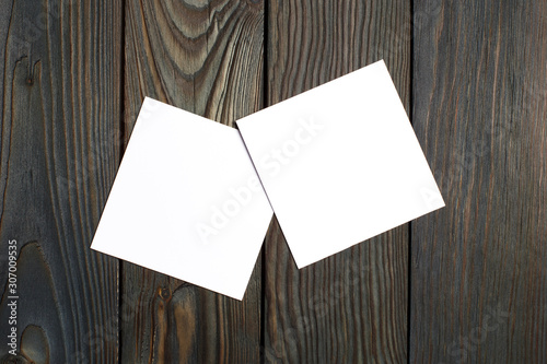 Fototapeta Two square blank cards (business cards, tickets, flyers, invitations, coupons, banknotes, etc.) on dark wooden background obraz