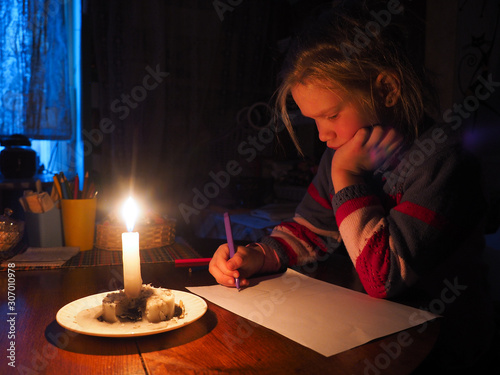 Photo little girl draws by candlelight