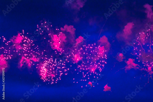 Foto auf Leinwand Violett Inexpensive fireworks, over the city, red and blue. Motion blur. Light flares. For any purpose