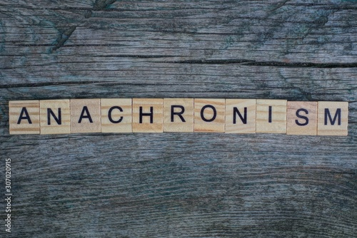 Photo word anachronism made from  wooden letters lies on a gray background