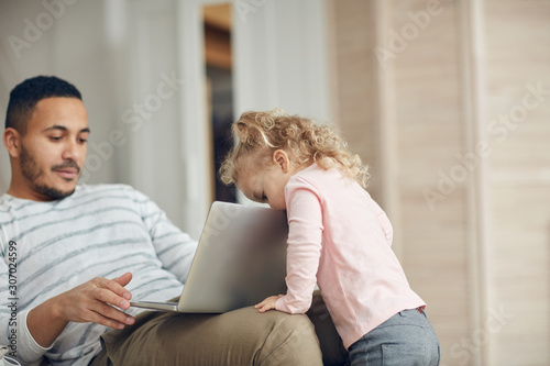 Fototapeta Portrait of cute little girl peeking at laptop screen while watching dad work from home, copy space obraz