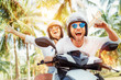Happy smiling couple travelers riding motorbike scooter in safety helmets during tropical vacation under palm trees