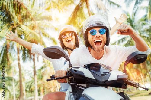 Obraz Happy smiling couple travelers riding motorbike scooter in safety helmets during tropical vacation under palm trees - fototapety do salonu