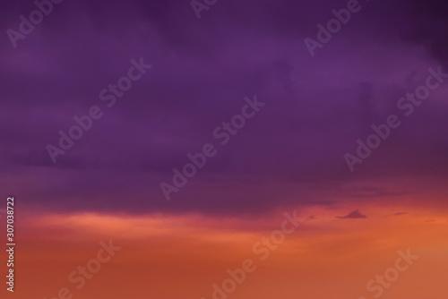 Foto auf Leinwand Violett Brilliant orange sunset and sunrise beautiful over dark blue clouds with orange sun on a cool spring morning.