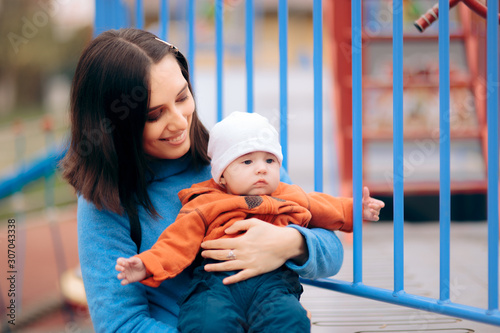 Mother Holding her Baby Outdoors in a Playground Wallpaper Mural