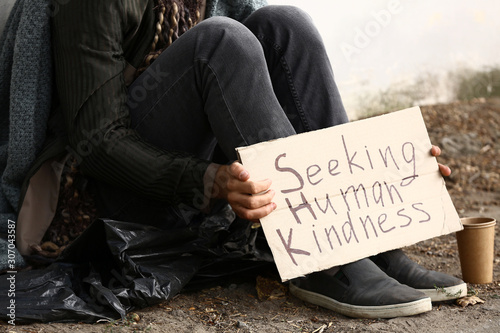 Fotomural Poor homeless man holding cardboard with text SEEKING HUMAN KINDNESS outdoors