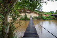 A Small Wooden Suspension Bridge For People Traveling Across The River In Chiang Mai, Thailand