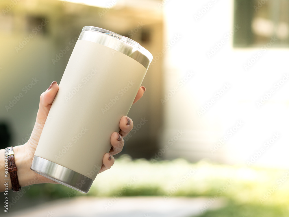 Fototapeta Closeup hand of a woman holding a reusable insulated stainless steel tumbler to show awareness of 'Say No to single use plastic' and 'Zero Waste' in outdoor area of cafe.