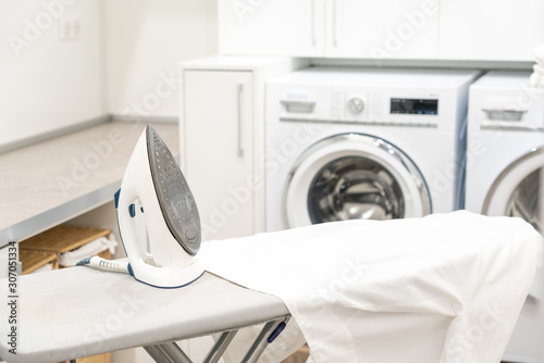 Photo Ironing board with white shirt and iron in laundry room