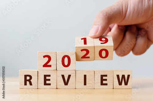 Spoed Foto op Canvas Europa 2020 review concept. Hand flip wood cube change year 2019 to 2020 and the word REVIEW on wooden block on wood table