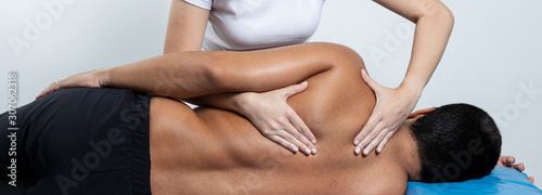 Fényképezés Close up of female osteopath doing shoulder blade therapy on young mam