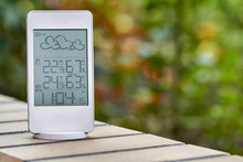 Best Personal Weather Station Device With Weather Conditions Inside And Outside On Foliage Background. Home Digital Weather Forecast Concept With Temperature And Humidity.