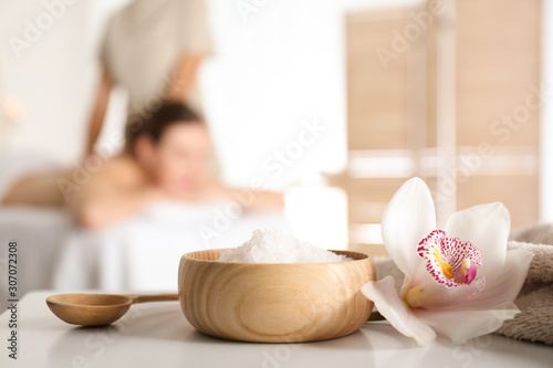 Bowl with sea salt and orchid flower on white table in spa salon. Space for text
